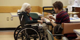 Tamara Rusoff-Hoen, right, talks with her mother, Louise Irving, at The Hebrew Home of Riverdale, in New York, Wednesday, March 25, 2015. The nursing home in the Bronx has started a pilot program in which relatives record video messages for patients of Alzheimer's and other forms of dementia. The videos are played for them each morning to calm their agitation and reassure them about their surroundings and their routines. (AP Photo/Richard Drew)