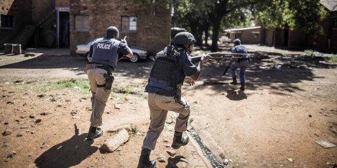Des policiers sud-africains à la recherche d'assaillants qui ont pris à partie des commerçants étrangers en leur criant de quitter l'Afrique du Sud, à Benoni, une localité à quelques kilomètres à l'est de Johannesburg.