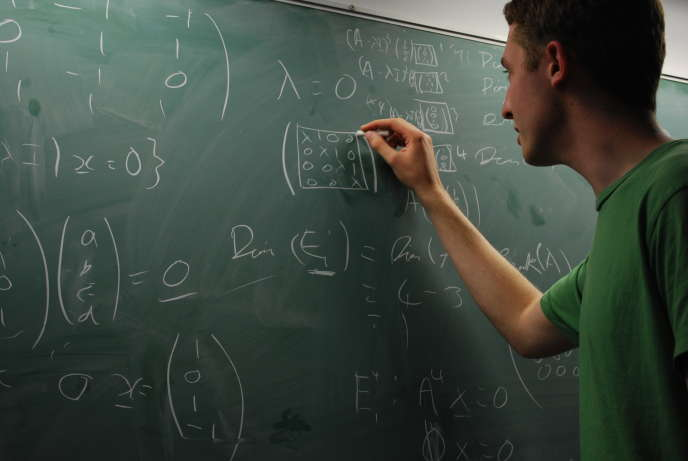 Un étudiant de Warwick (Angleterre) résout des équations mathématiques au tableau à la craie, le 12 octobre 2008.