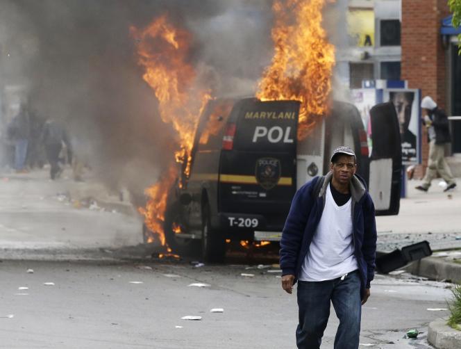 Un homme passe devant un véhicule de police incendié à Baltimore, le 27 avril.