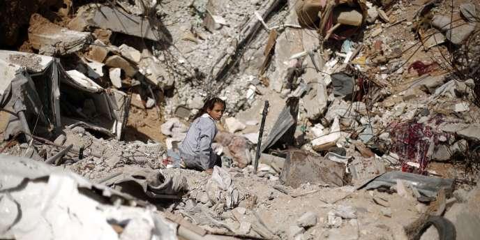 Une écolière palestinienne assise sur les ruines d'une maison, à Gaza, le 28avril.