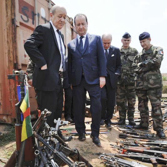 Le président François Hollande et Jean-Yves Le Drian, devant des armes confisquées par des militaires de l'opération «Sangaris», dans une base française à Bangui, en Centrafrique, en février 2014.