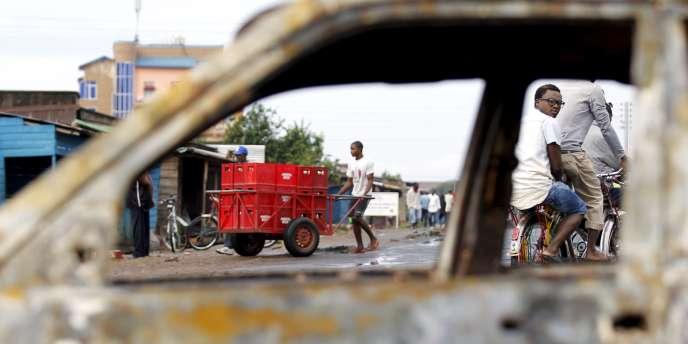 Des Burundais passent, le 2 mai, devant les restes d'une voiture calcinée, vestiges des affrontement violents qui sont survenus la veille dans la capitale, Bujumbura.