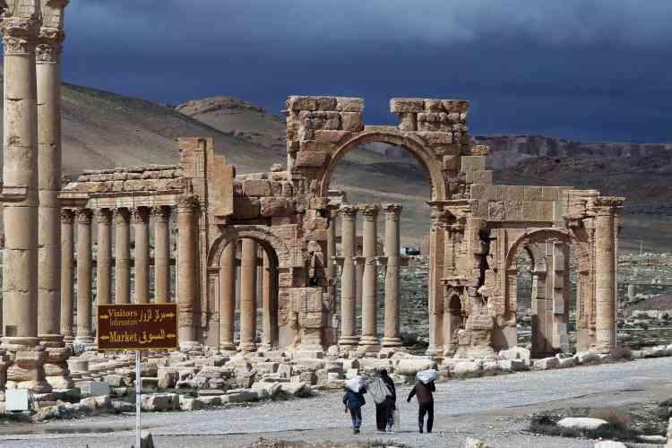 """Des Syriens marchent au milieu l'ancienne """"oasis caravanière"""", établie lorsque la cité entra sous contrôle romain dans la première moitié du Ier siècle, poursuit l'Unesco."""