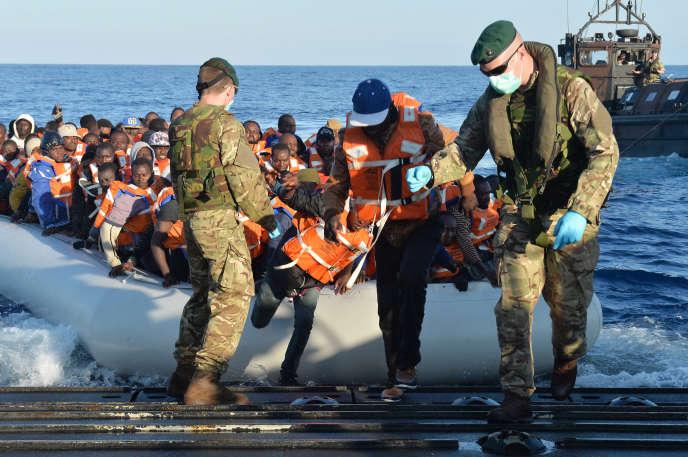 Des soldats de la marine anglaise aident des migrants à descendre d'un canot de sauvetage après avoir été sauvés d'un naufrage au large des cotes de Libye, le 13 Mai 2015.