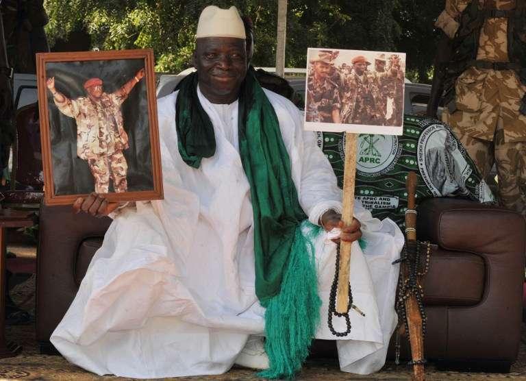 Le dictateur gambien Yahya Jammeh pose fièrement, en 2011, avec des photos de lui en ancien soldat.