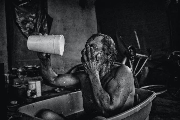 Un chômeur prenant son bain dans une bassine, à Lanare (2014).