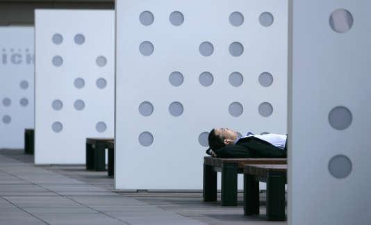 Un businessman fait la sieste sur un banc à Tokyo le 8 juin 2007.