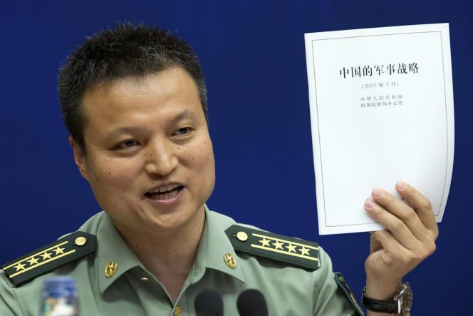 Le porte-parole du ministère de la défense chinois, Yang Yujun, présente un exemplaire du Livre blanc sur la stratégie militaire chinoise lors d'une conférence de presse mardi 26 mai à Pékin.