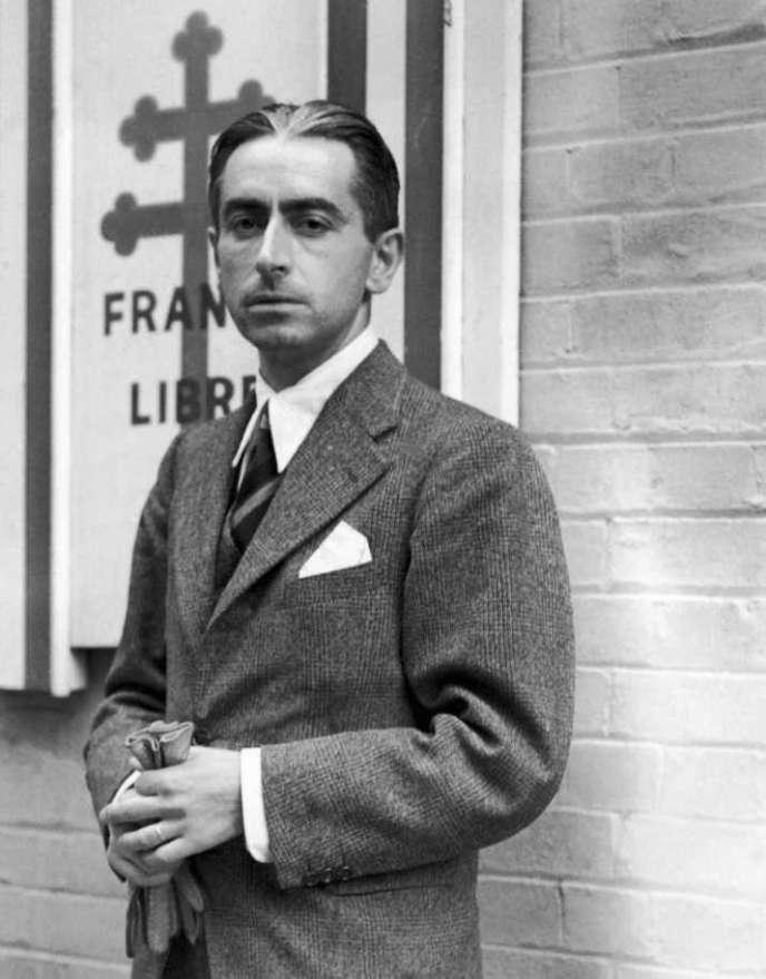 Le résistant français Pierre Brossolette, debout devant un drapeau de la France libre, à Londres, entre 1942 et 1944.