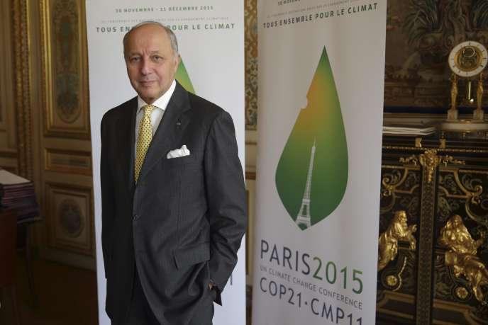 Le ministre des affaires étrangères, Laurent Fabius, vendredi 22 mai, devant l'affiche de la 21e conférence de l'ONU sur le climat, qui se déroulera en décembre à Paris.