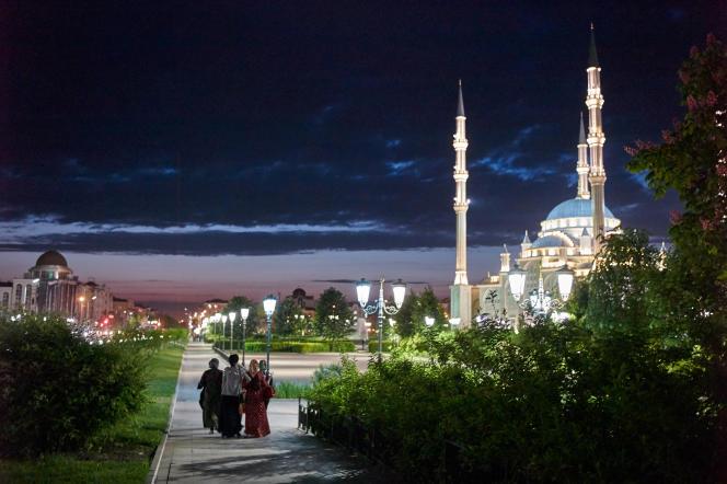 Des femmes marchent la nuit dans le centre de Grozny, dans le parc qui entoure la mosquée