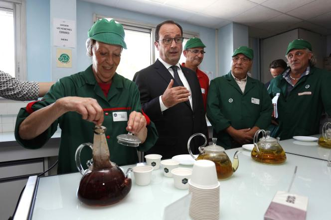 French President Francois Hollande (C) gets a cup of tea as he visits with former employees of Fralib company in Gemenos, France, June 4, 2015. The employees recently launched their own brand of teas and infusions, named