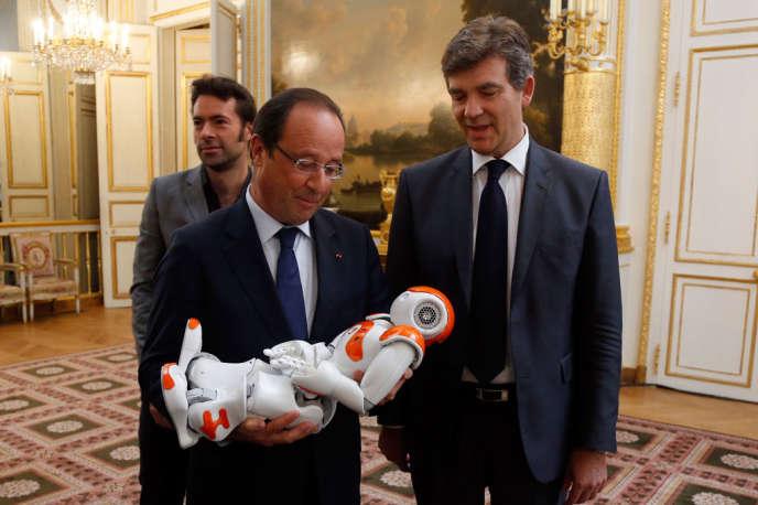 Le robot doit ressembler le plus possible à un humain – sans en être un, donc – pour que sa relation avec un être de chair et de sang soit la meilleure possible(photo: François Hollande, aux côtés d'Arnaud Montebourg, tient dans ses bras le robot