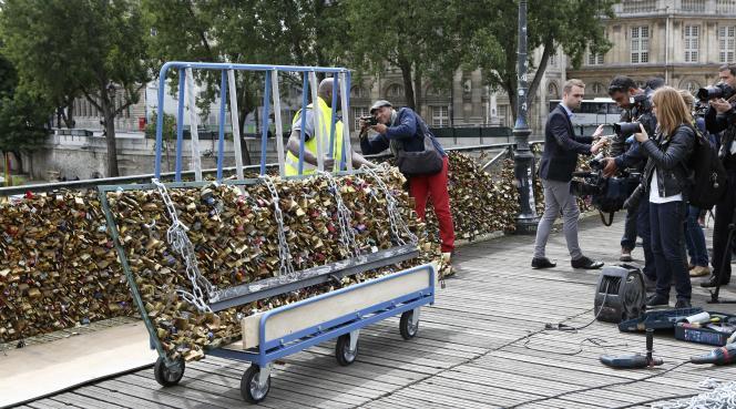 Les services de la ville de Paris enlèvent les grilles de cadenas sur le pont des Arts, en juin 2015.