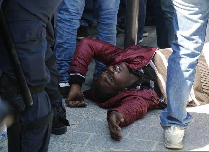 Un migrant arrêté par la police reste à terre, lundi 8 juin.