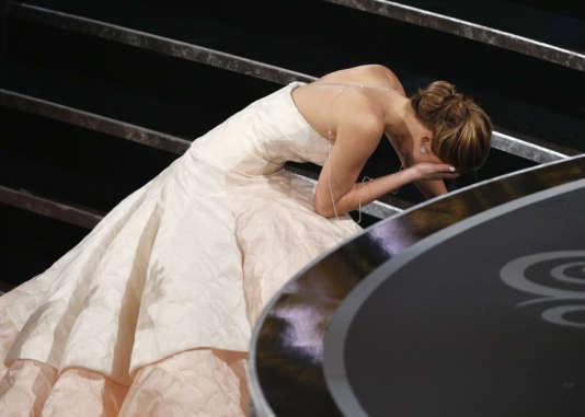 """Jennifer Lawrence s'empêtre dans les plis de sa robe longue  en venant chercher son Oscar de la meilleure actrice pour son rôle dans """"Happiness Therapy"""" (2013)."""