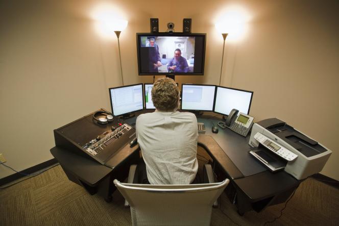 Le docteur Oscar Boultinghouse, dans son bureau a Houston, ausculte sur écran un œil du patient Charles Martin qui est à bord d'une plate forme pétrolière en mer de Chine méridionale, au large de la Malaisie.  ecrans, ordinateur, loupe, webcam, auscultation, video, medecine, progres technologique, technologie, communication, internet