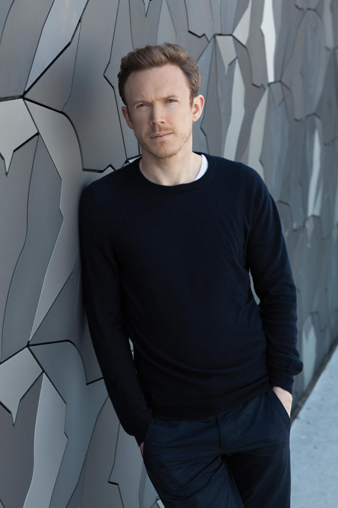 Daniel Harding devant le mur d'oiseaux de la Philharmonie de Paris.
