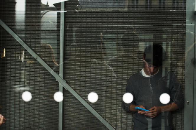 Un lycéen en pause, juste derrière la vitre qui le sépare du balcon de la bibliothèque.