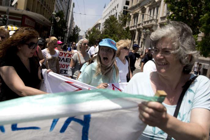 Des personnels d'entretien des écoles publiques, qui manifestent pour obtenir des contrats à durée indéterminée, lancent des slogans contre le gouvernement, lundi 15 juin, à Athènes.