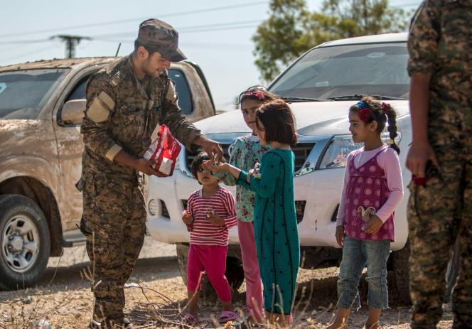 Un combattant kurde distribue des bonbons à des enfants, près de Rakkaa, en Syrie, le 16juin.