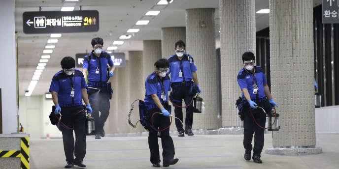 Des employés désinfectent le parking de l'aéroport international de Gimpo à Séoul, le 17 juin.