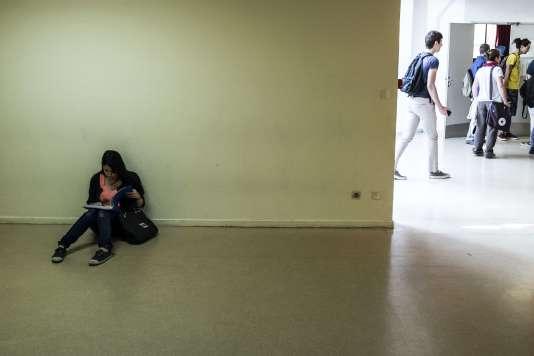 Une lycéenne sors ses cahiers pour des révisions de dernière minute avant l'examen de philosophie du baccalauréat, le 17 juin 2015 au lycée Aragon, à Givors.