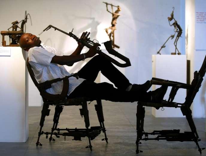 Le sculpteur Gonçalo Mabunda au milieu de quelques-unes de ses oeuvres réalisées à partir d'armes recyclées.