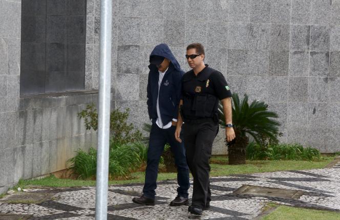 Un suspect arrive au quartier général de la police fédérale à Sao Paulo vendredi 19 juin, escorté par un officier.