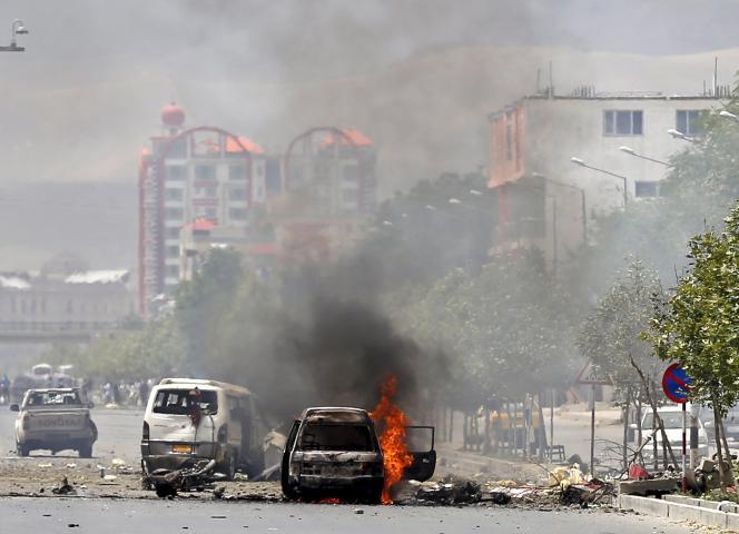 Un véhicule en flammes devant l'entrée du Parlement afghan, le 22 juin 2015.