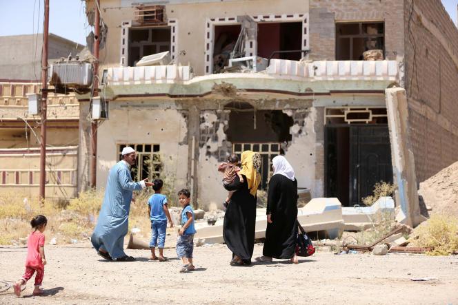 Une famille d'Irakiens déplacés passe devant les ruines d'une maison, à Tikrit, le 21 juin.