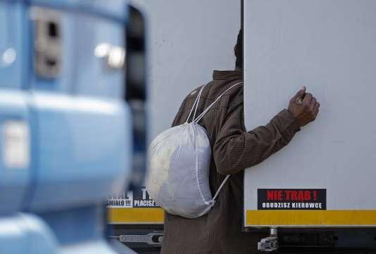 Un migrant inspecte un camion afin de traverser illégalement le tunnel sous la Manche en direction de la Grande-Bretagne.