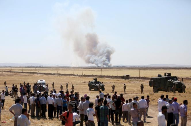 Des civils observent les combats dans Kobané depuis la Turquie, jeudi 25 juin 2015.