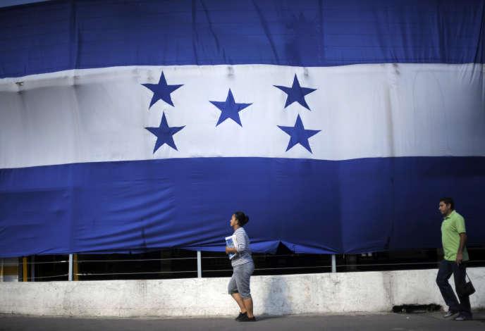 A woman and a man walk past a giant Honduran flag in Tegucigalpa September 28, 2012.  REUTERS/Jorge Cabrera (HONDURAS - Tags: SOCIETY) - RTR38K97