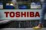 Pedestrians walk past a logo of Toshiba Corp outside an electronics retailer in Tokyo, Japan, June 25, 2015. Toshiba Corp may appoint more outside board members to help prevent a recurrence of accounting irregularities that are currently under investigation, the company's CEO said on Thursday. REUTERS/Yuya Shino