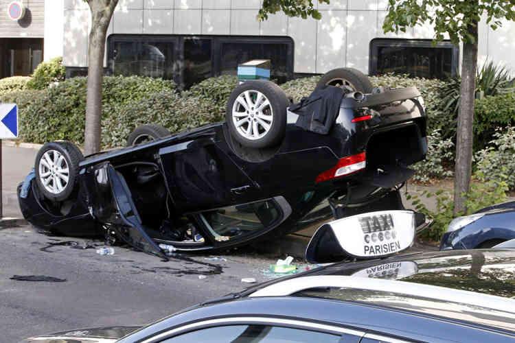 Une voiture, renversée pendant les échauffourées, porte Maillot.