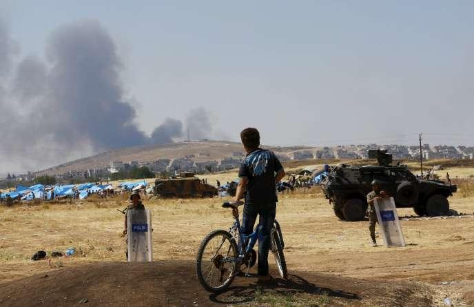 Un jeune turc à la frontière avec la Syrie, à Suruç, regarde la fumée s'élever de la ville de Kobané, le 27 juin.