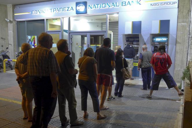 Des Grecs font la queue vendredi soir pour retirer un peu d'argent aux distributeurs.