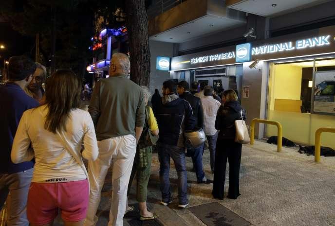 Devant des distributeurs de billets, à Athènes, samedi 27 juin.