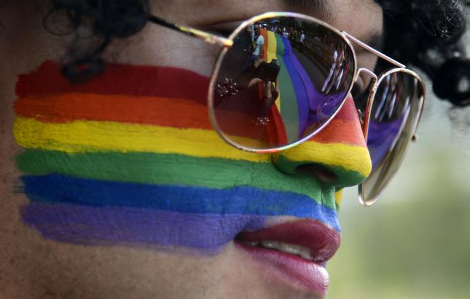TOPSHOTS A giant rainbow flag is reflected on a reveler's sunglasses during the Gay Pride Parade in Medellin, Antioquia department, Colombia on June 28, 2015. AFP PHOTO / Raul ARBOLEDA