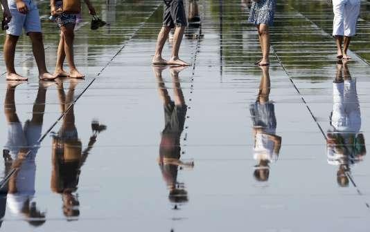 Des passants se baladent pieds nus au niveau du miroir d'eau, à Bordeaux, le 30 juin 2015.