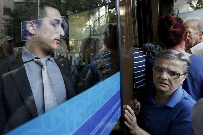 Avec une baisse de 30 % de la demande depuis le dernier point haut cyclique et une hausse du chômage à plus de 25 %, l'économie grecque est loin d'être capable de rembourser ses dettes (photo: un employé maintient fermée la porte de son agence bancaire le 1er juillet, à Athènes).