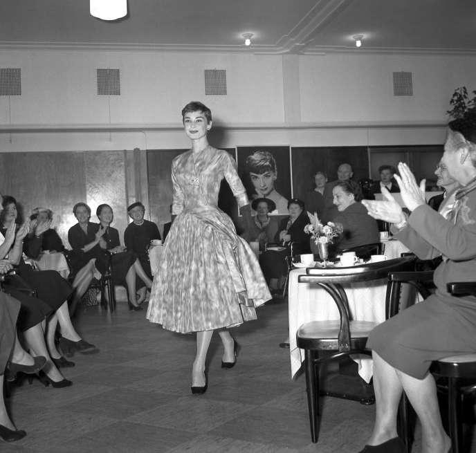 L'actrice Audrey Hepburn présente une création du couturier Hubert de Givenchy, lors d'un défilé de mode, en novembre 1954, à Amsterdam.