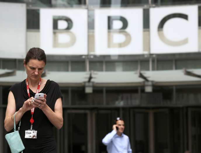 People stand outside Broadcasting House, the headquarters of the BBC, in London Britain July 2, 2015. The BBC said it will cut more than 1,000 jobs because it expects to receive 150 million pounds ($234 million) less than forecast from the licence fee next financial year as viewers turn off televisions and watch programmes on the Internet.  REUTERS/Paul Hackett