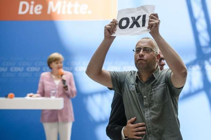 Un homme brandit un papier qui clame NON en grec, la veille du référendum. Angela Merkel donnait un discours dans le cadre d'un meeting de la CDU, à Berlin le 4 juillet.