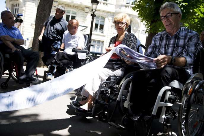 Manifestation de personnes en fauteuil roulant, réclamant une meilleure accessibilité pour les handicapés moteurs, à Paris, le 6 juillet 2015.
