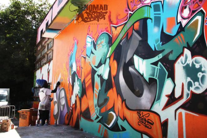 Le Sénégalais Docta, l'un des premiers graffeurs africains, devant une de ses oeuvres.