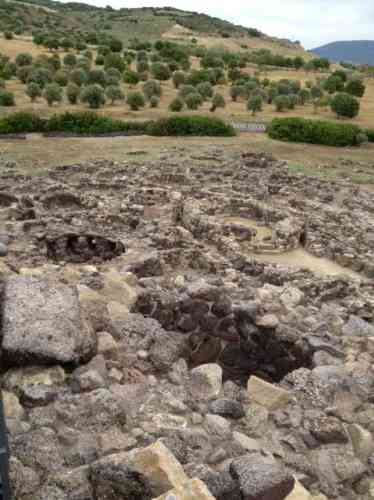 Vue du sommet du site de Barumini, bordé de champs de blé et d'oliviers. On aperçoit les murets circulaires du village plus tardif. Et au premier plan, est visible le sommet de la fausse coupole – le tholos – dont la pierre qui sert de « couvercle » a été déplacée sur la gauche de l'ouverture.
