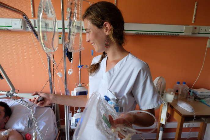 Une infirmière change la perfusion d'un patient au service de soins palliatifs du Groupe hospitalier Diaconesses, à Paris.